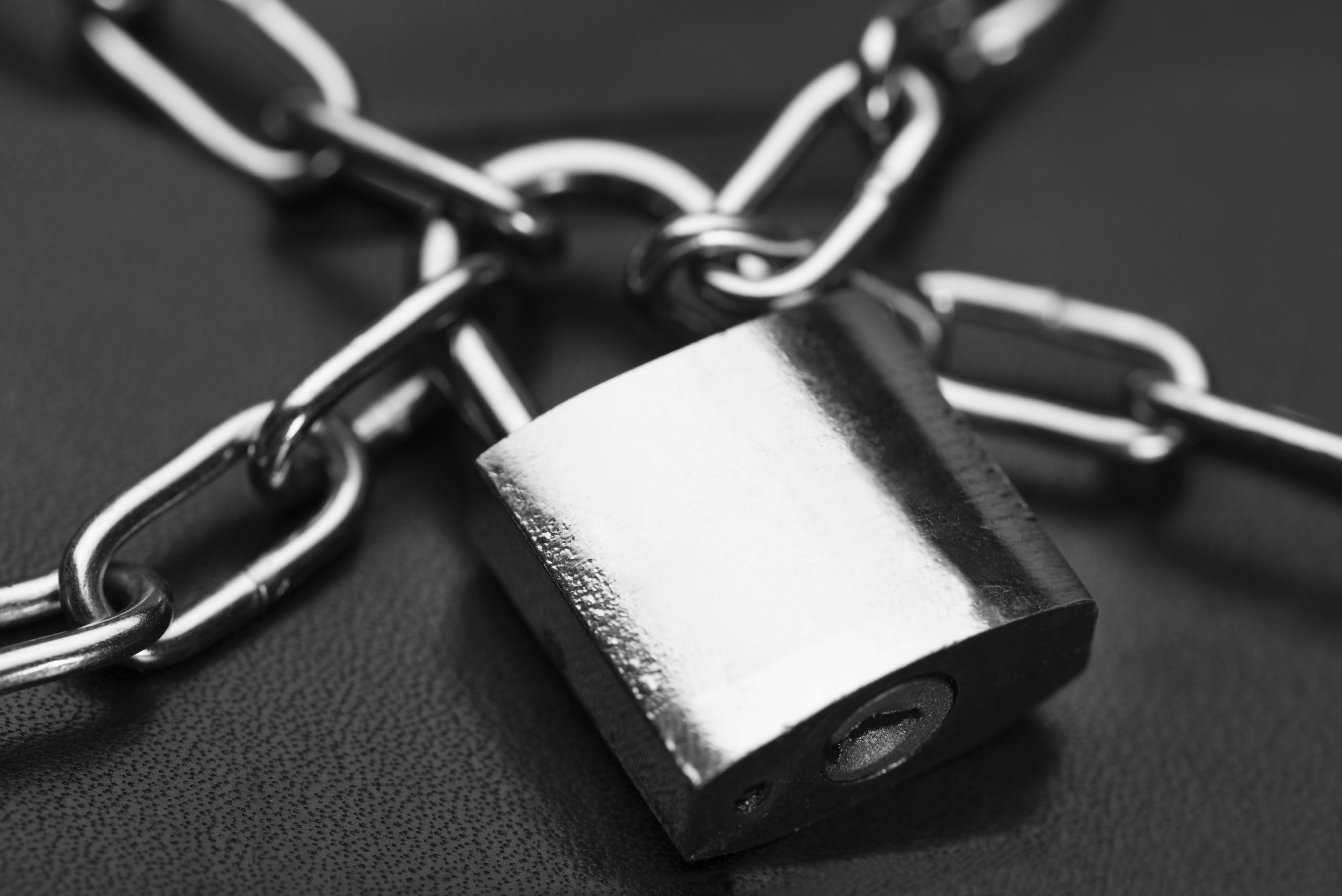 Closeup of metallic padlock and chains against black background