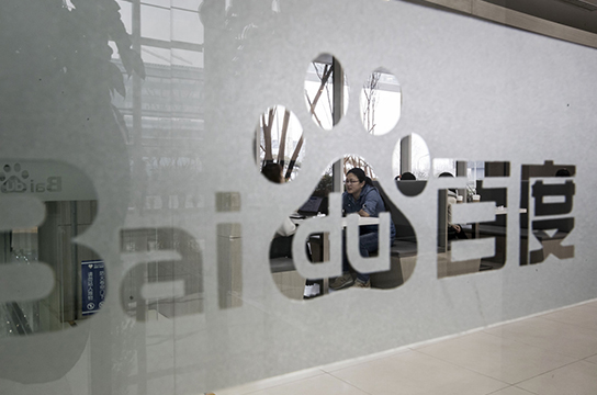 Signage for Baidu Inc. is displayed on a window at the Baidu Technology Park in Beijing, China, on Friday, Nov. 25, 2016. Baidu serves 6 billion searches a day and dominates mobile mapping, which gives location data for its mobile users as well as those of apps built on its map data. Photographer: Qilai Shen/Bloomberg via Getty Images