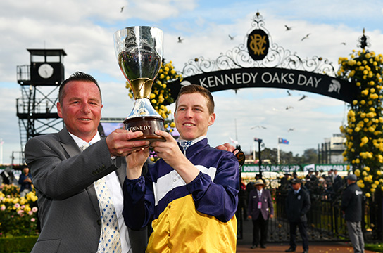 MELBOURNE, AUSTRALIA - NOVEMBER 08: Damian Lane and Trainer Matthew Ellerton pose with Kennedy Oaks trophy after Aristia won in Race 8,  Kennedy Oaks  during Oaks Day at Flemington Racecourse on November 08, 2018 in Melbourne, Australia. (Photo by Vince Caligiuri/Getty Images)