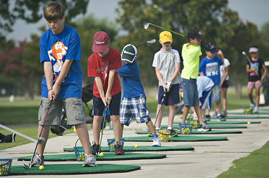A line of children play golf during the annual Junior Golf Clinic on the Oaks Golf Course at Randolph Air Force Base, Joint Base San Antonio, Texas, June 13, 2012. The clinic is a recreational activity to teach children of U.S. Service members or Department of Defense civilians the basics of golf and course etiquette. (U.S. Air Force photo by Benjamin Faske/Released)